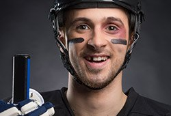 Man in hockey gear with missing tooth