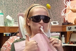 Patient brushing teeth in dental chair