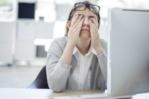 woman rubbing her eyes in front of computer