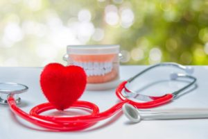 Small heart shape, stethoscope, model teeth, and dental tools on table