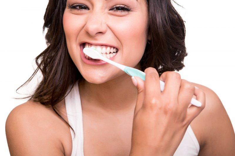 woman brushing teeth anticipating visit to dentist in Stephens City