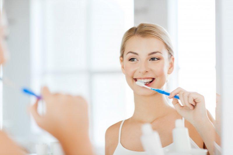 Woman smiling while brushing her teeth