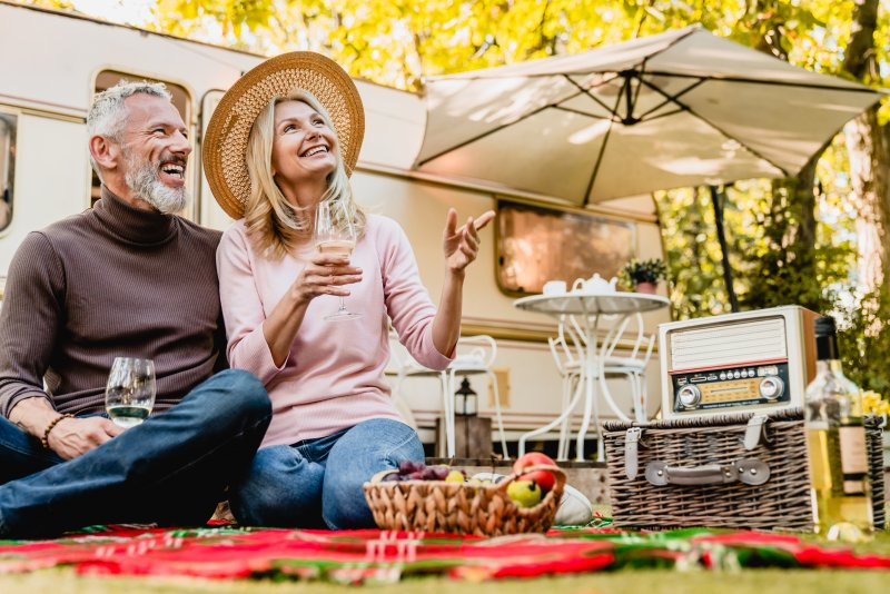 Mature couple talking and smiling during summer picnic
